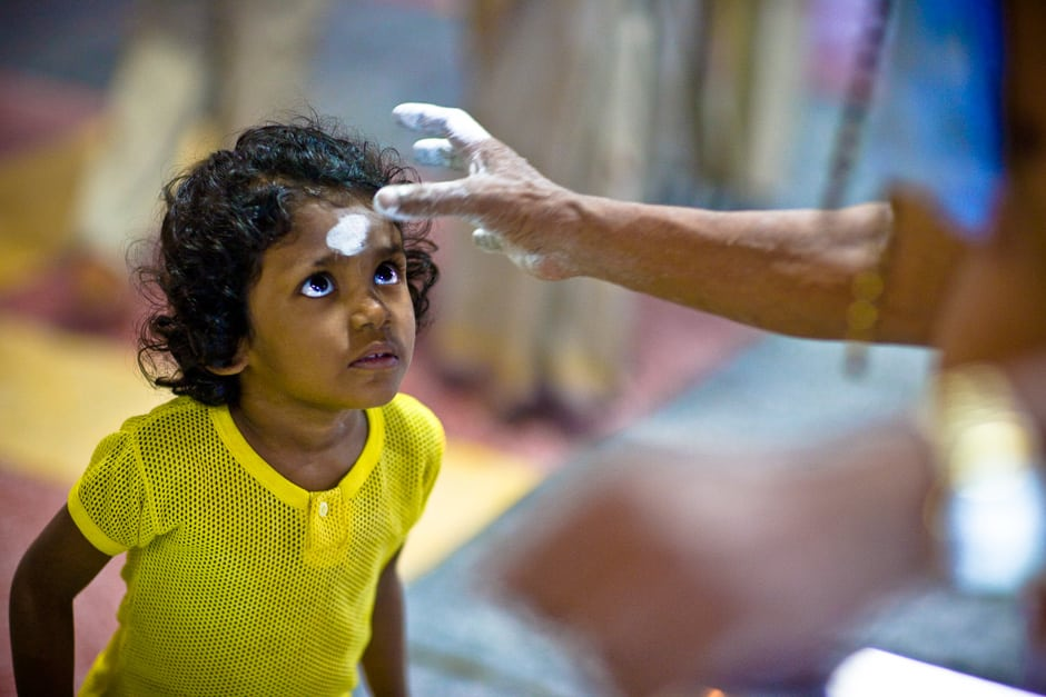 A child devotee of the Hindu god, Murugan receives a tilaka of ash from a priest, during Thaipusam. Penang, Malaysia