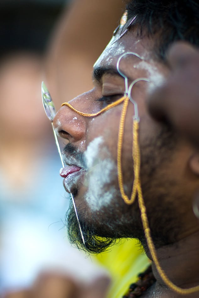 Devotees begin the piercing of their tongues and cheeks for their walk to the temple.