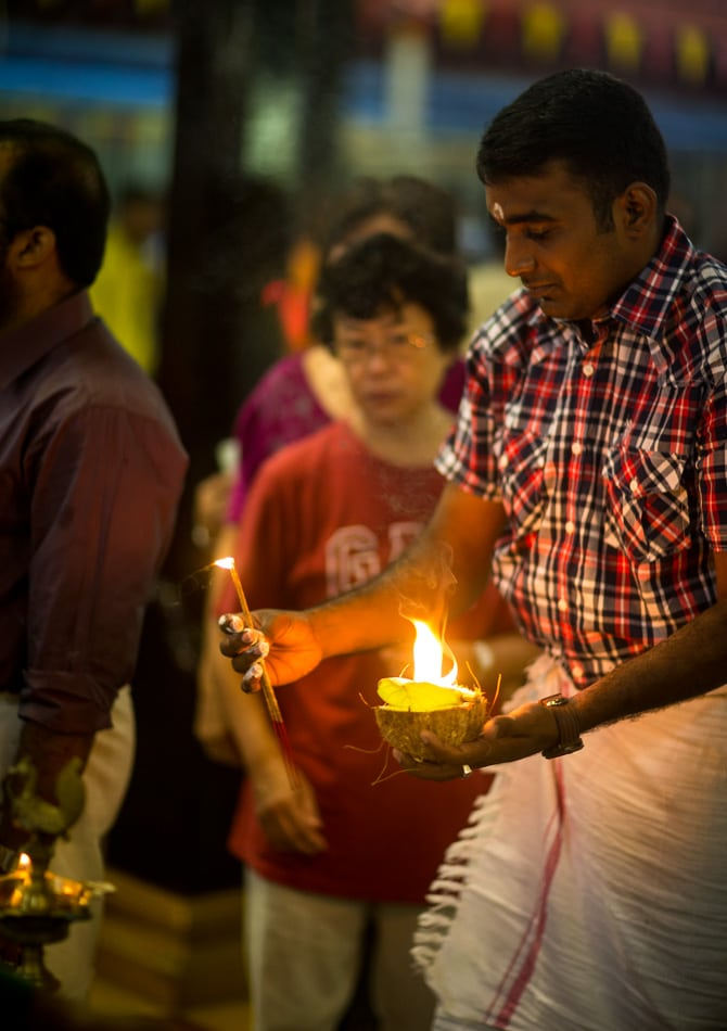 A priest lights a coconut to give to a devotee to offer the idol.