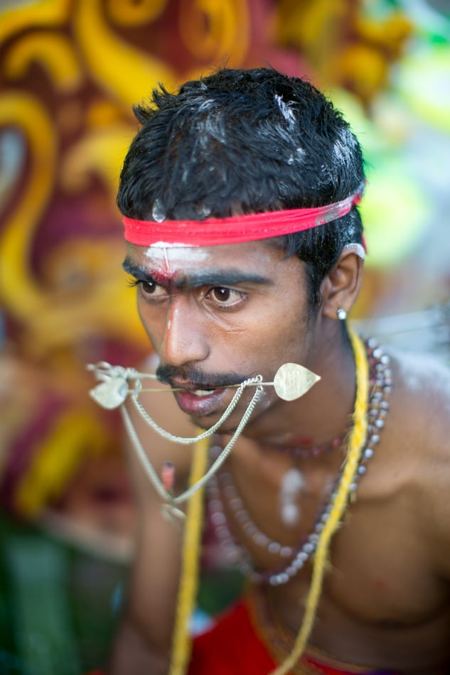 This devotee waits for the veil or hooks and spears to be removed from his body.