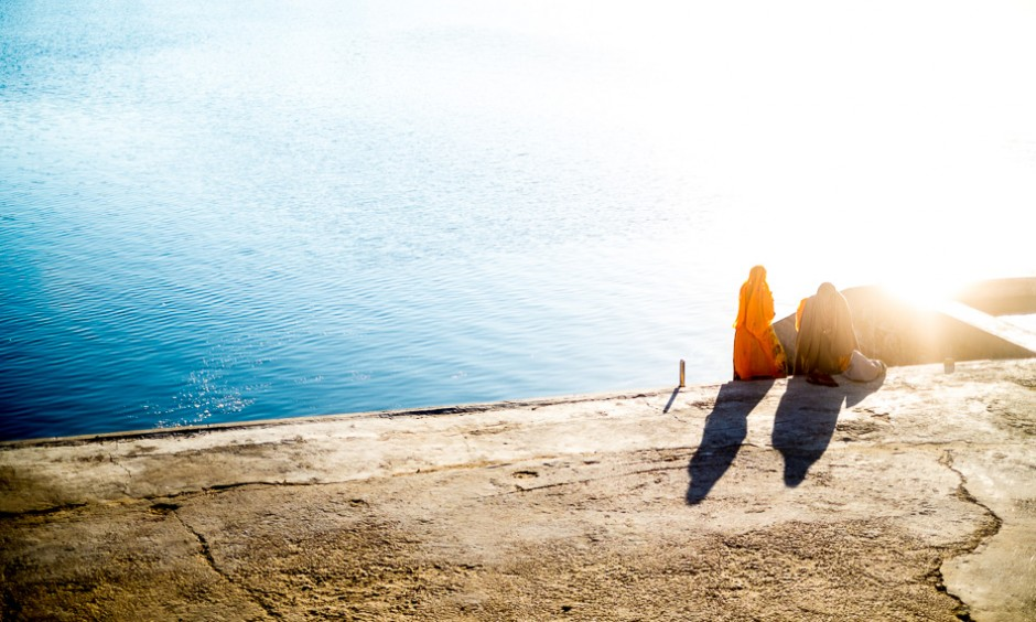 The early morning sun shines on two women at the bathing ghats around Pushkar Lake.