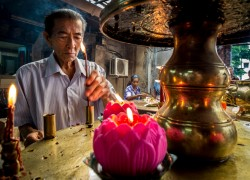 A Taoist man lights a candle at the Goddess of Mercy Temple in Georgetown, Penang, Malaysia. Does he care what I do with his image?