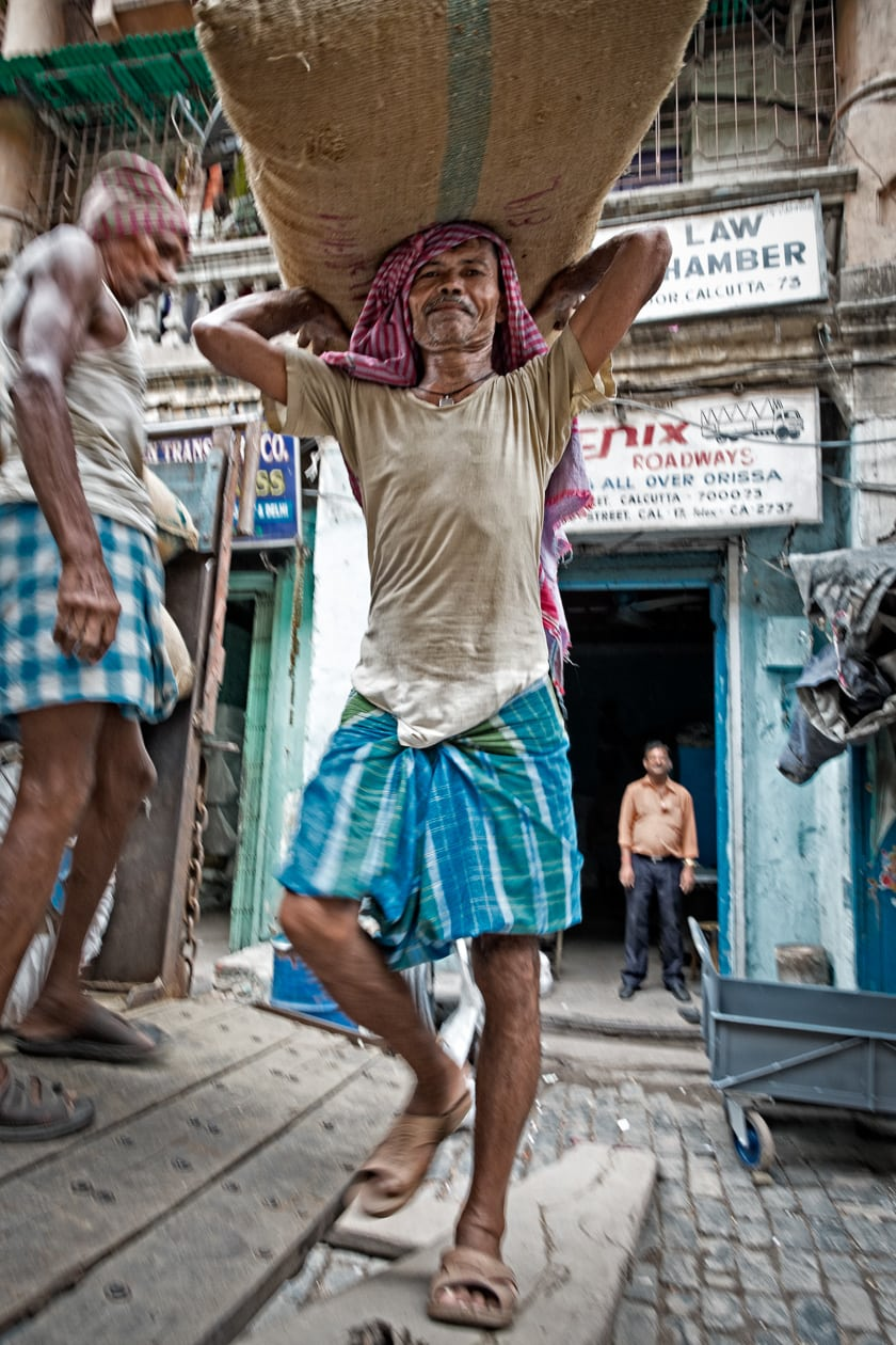 A man carries a heavy heavy burlap sacks on his head while loading a lorry full of goods.