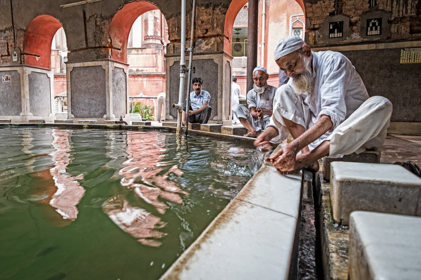 "A man performs ""wuzu"" or ritual washing before prayers at the Nakhoda Masjid."