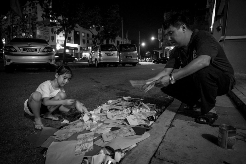 Kai Xin and her father spread the money loosely across pile to ensure that it all burns up.f/2.8, 1/20 sec, at 14mm, 3200 ISO, on a X-Pro1