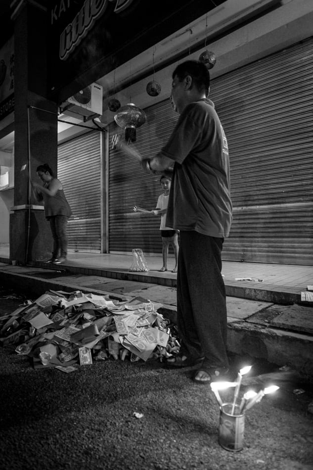 Mr Goh, Elsa and Kai Xin offer prayers to the hungry ghost waving the traditional joss sticks (Incense sticks).f/2.8, 1/17 sec, at 14mm, 3200 ISO, on a X-Pro1