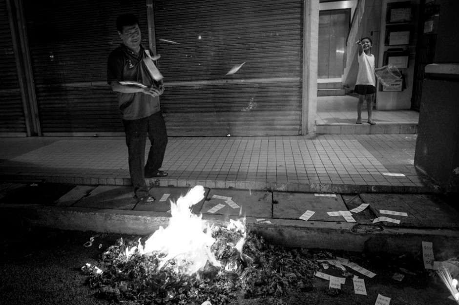 Kai Xin watches on with excitement as her father throws paper notes over the fire to burn.f/2.8, 1/30 sec, at 14mm, 2500 ISO, on a X-Pro1