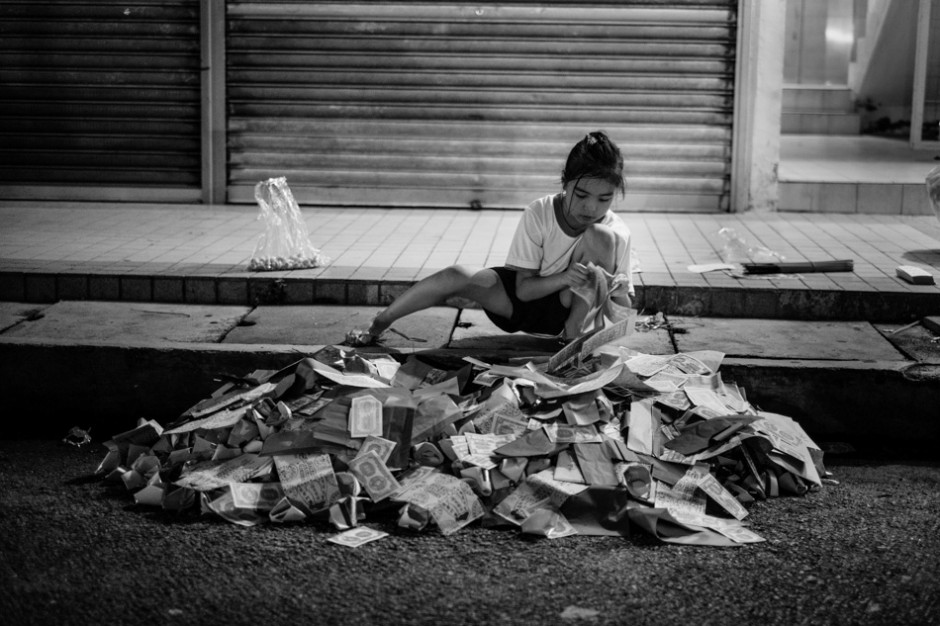 Kai Xin prepares her pile of money and life's accessories to be burnt for the hungry ghosts.f/1.4, 1/30 sec, at 35mm, 3200 ISO, on a X-Pro1