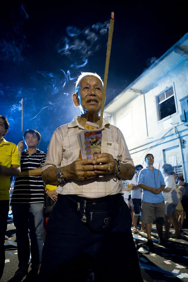 Taoist devotees pray with joss sticks before the King of Hell. f/2.8, 1/20 sec, at 14mm, 3200 ISO, on a X-Pro1